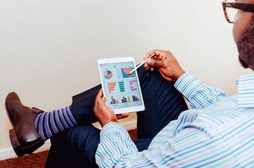 Photo d'un homme assis qui tient sa tablette numérique