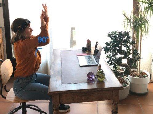 Photo d'une femme assise à son bureau qui s'étire les bras en faisant des mouvements croisés